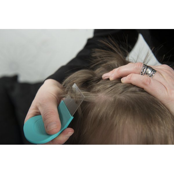 A woman using a nit comb to pull lice from a girl's hair.