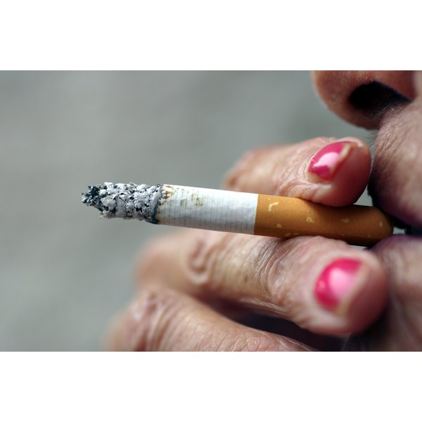 An older woman smokes a cigarette.