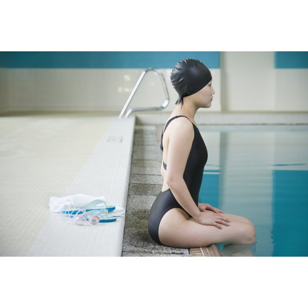 A young woman sitting on the edge of the pool, wearing a swim cap.