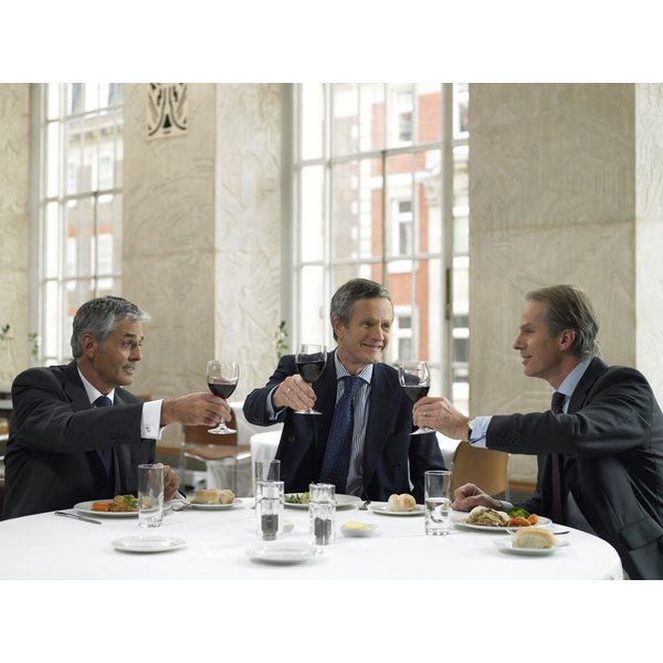 Men toasting at table with wine.