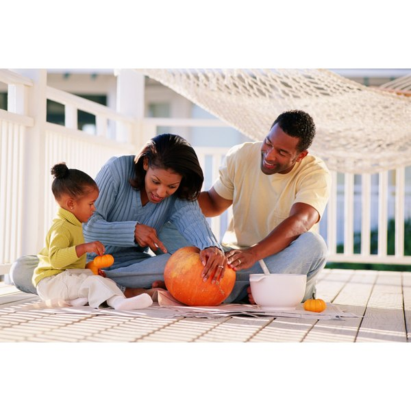 A young family is carving pumpkins and scooping out the inside.