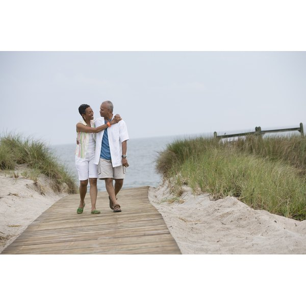 A couple talking as they walk on the beach.