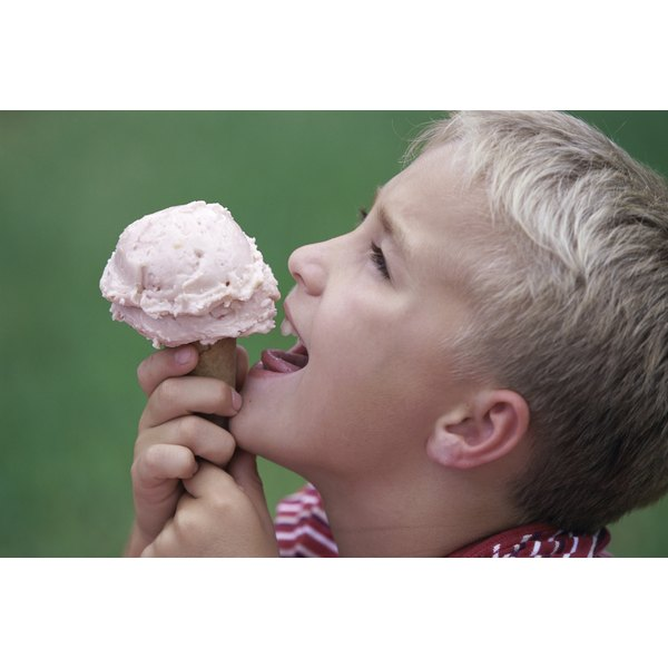 A young boy is eating an ice cream cone.