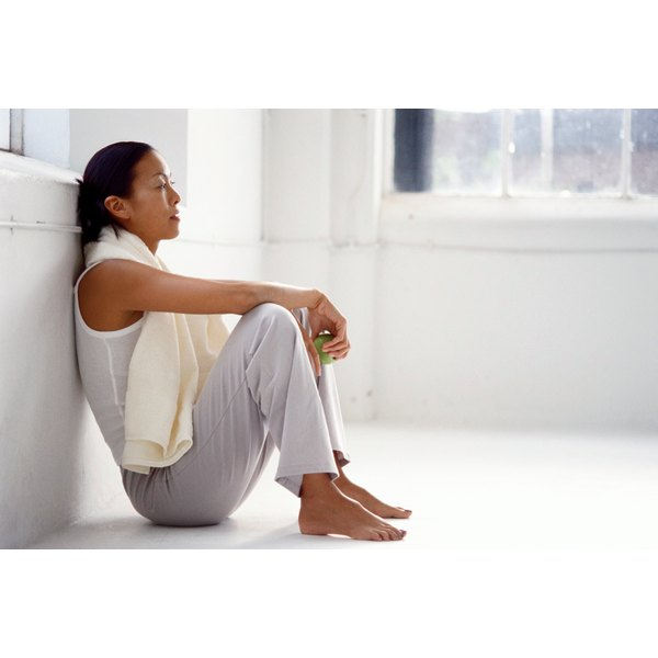 A woman is leaning against a wall with a towel around her neck.