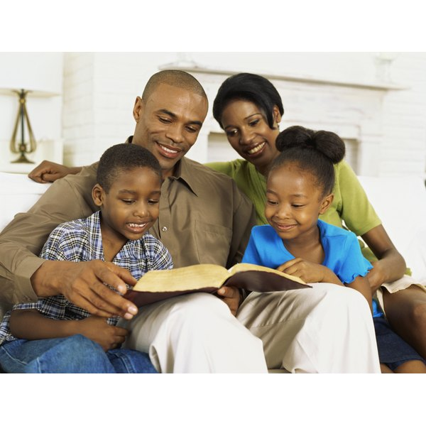 Two parents reading the Bible to their children.