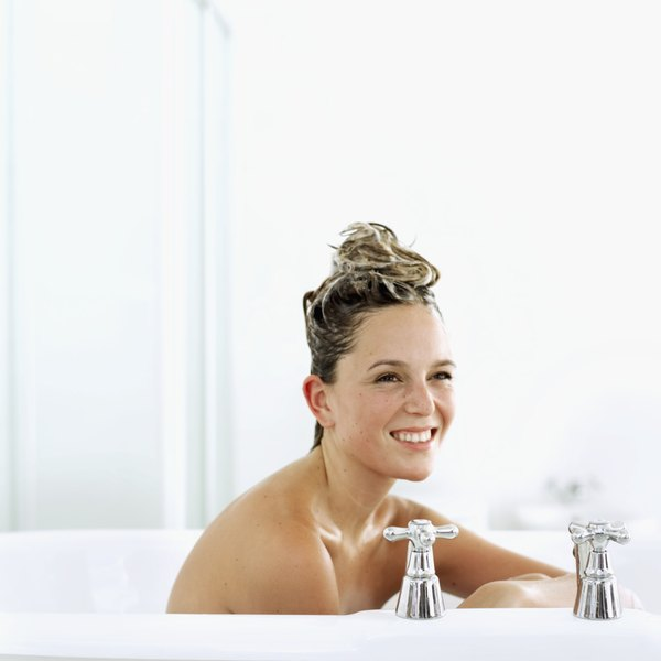 A young woman taking a bath with shampoo in her hair.