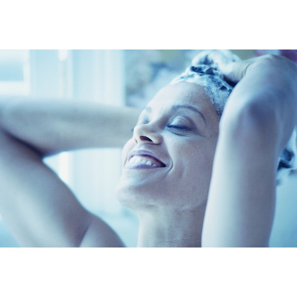 A woman smiles as she washes her hair in the shower.