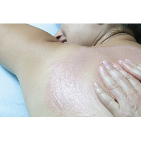 A young woman is having lotion rubbed into her back.