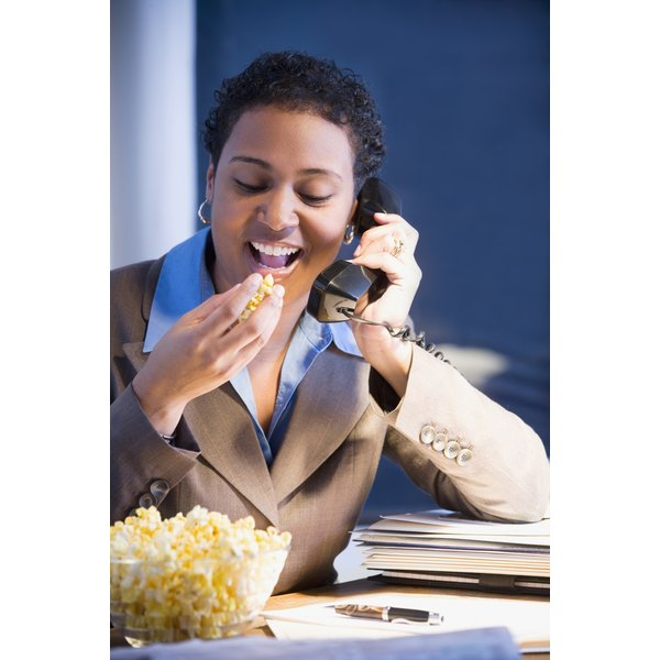 working woman eating bowl of popcorn at her desk while talking on phone