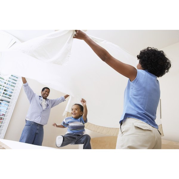 Toddler age boy jumping on the bed while parents wave sheet over his head.