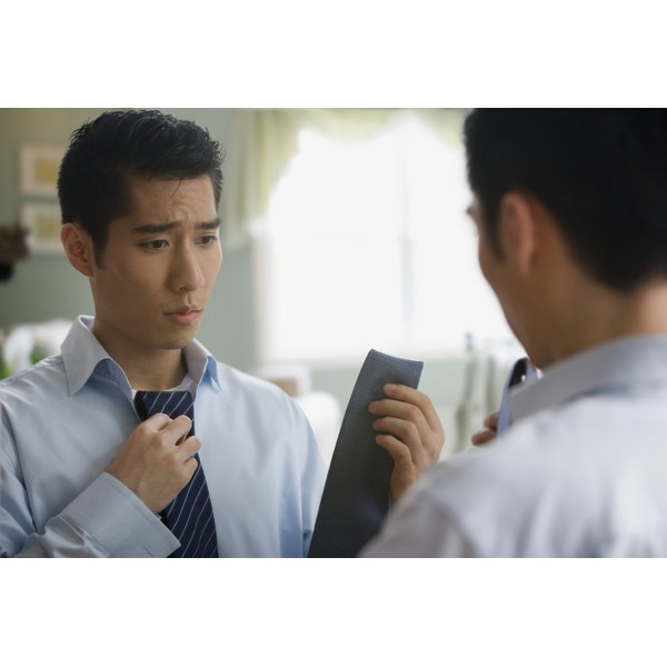Young man looking at neckties in a mirror.