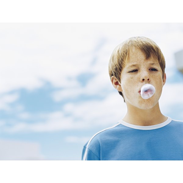 A boy is blowing a bubble.