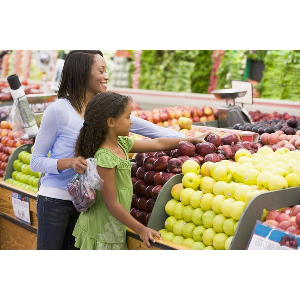 An African American mother and daughter shop for fruit in the produce section of a supermarket.