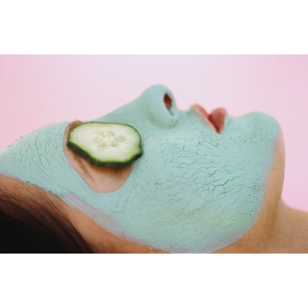 Woman with green face mask and cucumber over her eye