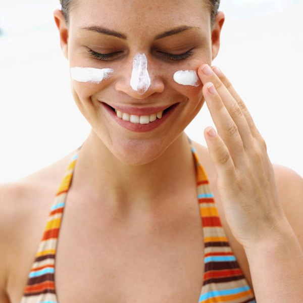 A woman in a bikini putting sunscreen on her face.