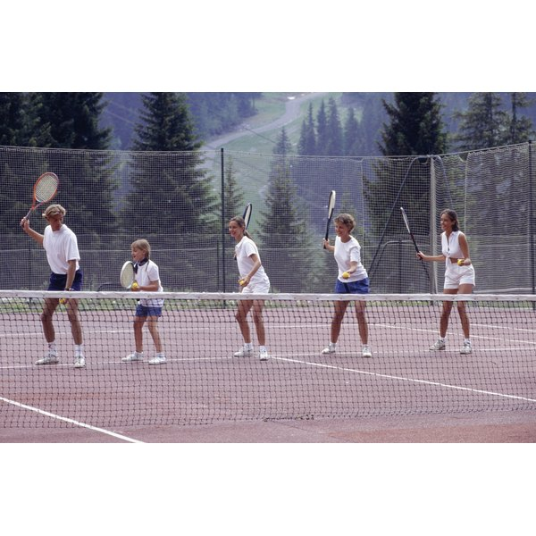 A group of young adults taking tennis lessons.