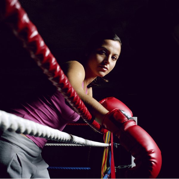 A young female boxer leans over the ropes of a boxing ring.