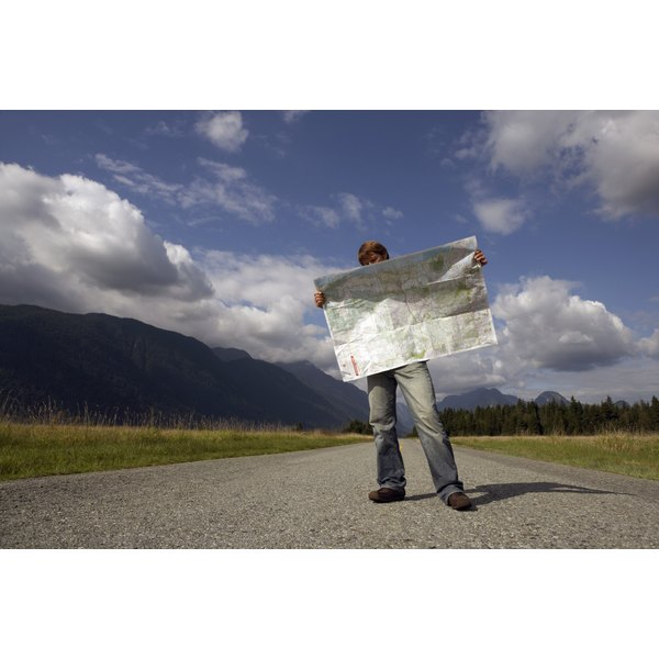A man holding a map on an empty road in the middle of nowhere.
