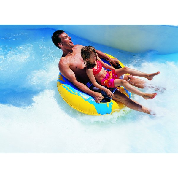 A father and child riding down a water slide.