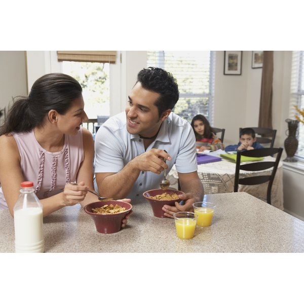 A couple eating cereal in the kitchen.