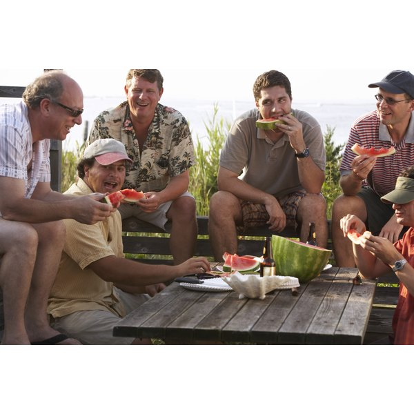 A group of men are eating watermelon.