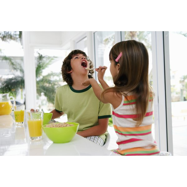 A young boy and girl are eating cereal.