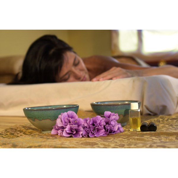 Woman laying on mattress beside small pile of essential oils.