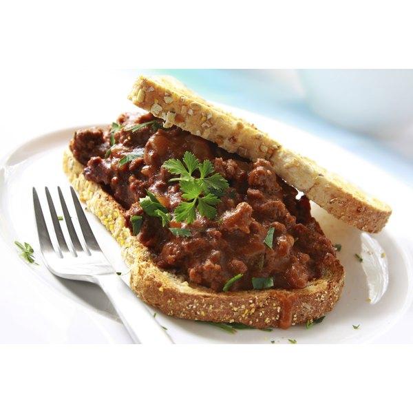A sloppy joe sandwich on toasted bread with a cilantro garnish.