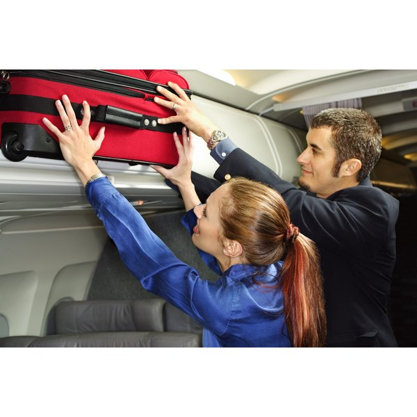 Check large bags or ask for help putting them in the overhead cabin.