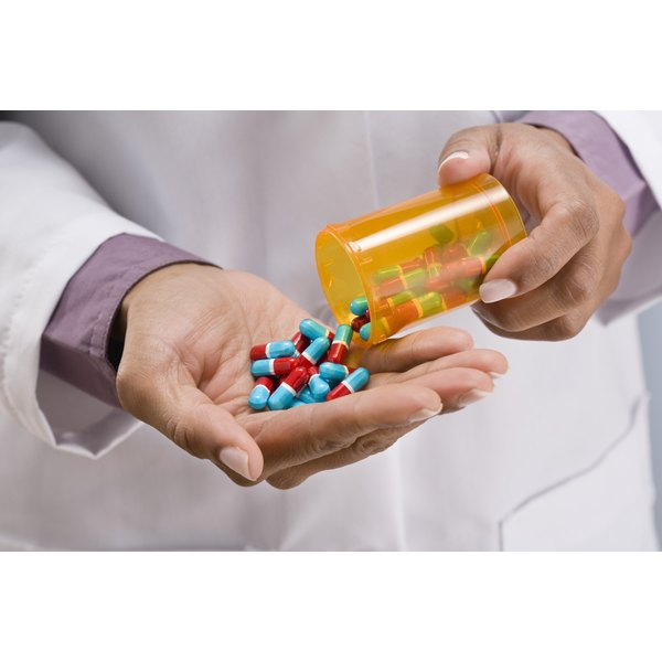 A pharmacist is pouring pills in his hand.