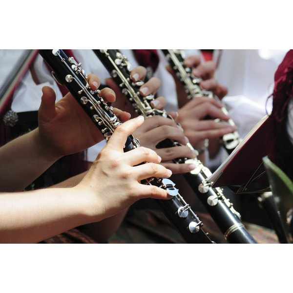 Three people playing the clarinet in an orchestra band.
