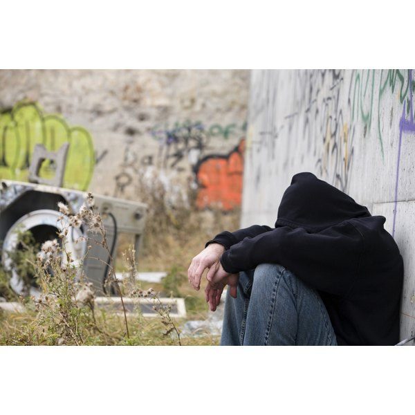 A depressed, homeless man leaning against a cement wall.