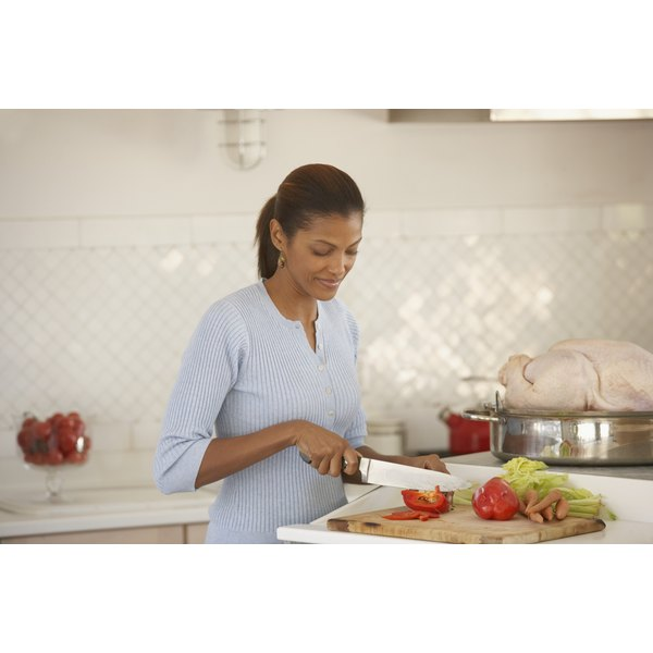 Woman slicing vegetables in kitchen.