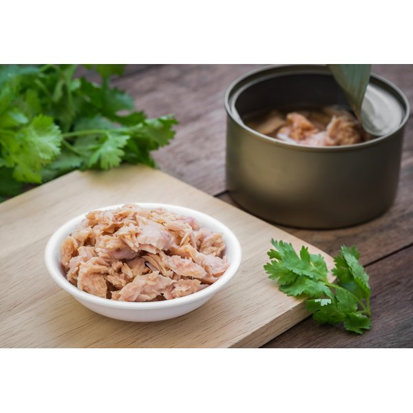 A bowl of canned tuna on a cutting board.