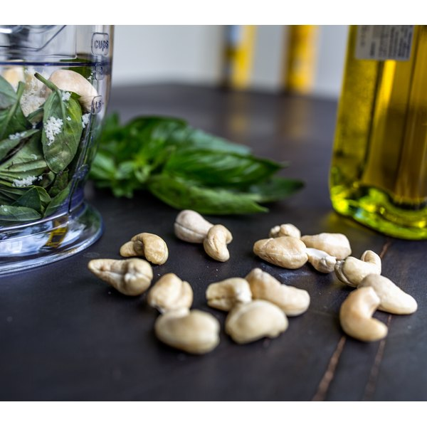 Raw cashews on a table with basil and olive oil.