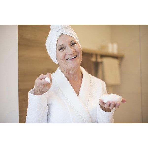 An elderly woman holding a jar of moisturizer.