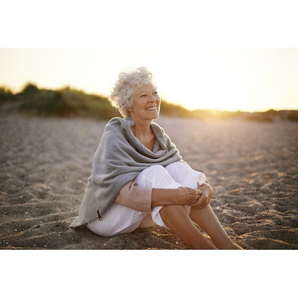 An elderly woman sitting on a beach.