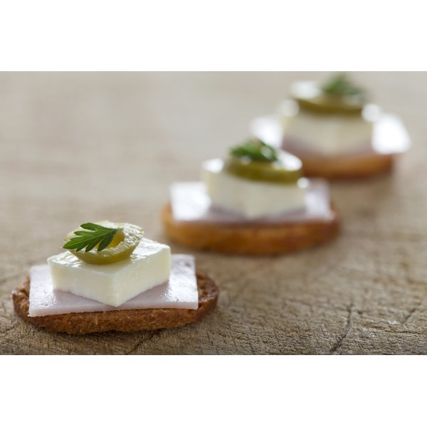 Cracker with white cheddar cheese, olive and meat.
