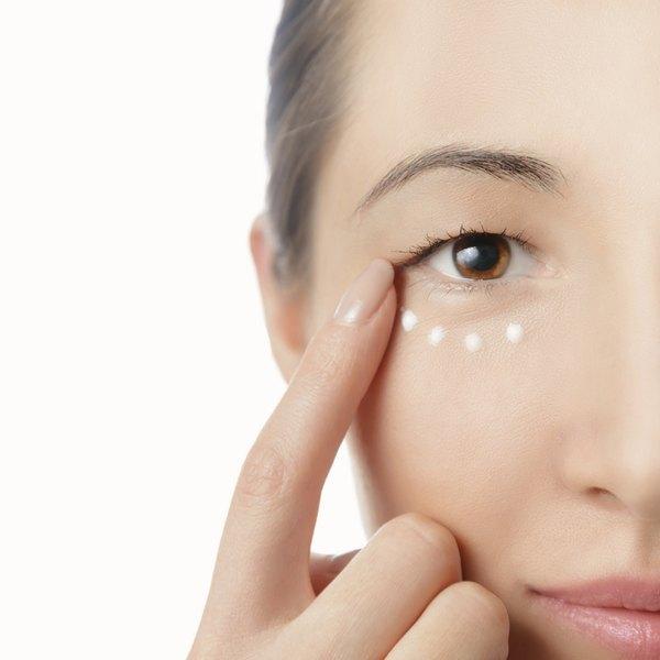 Woman applying eye cream under eye.