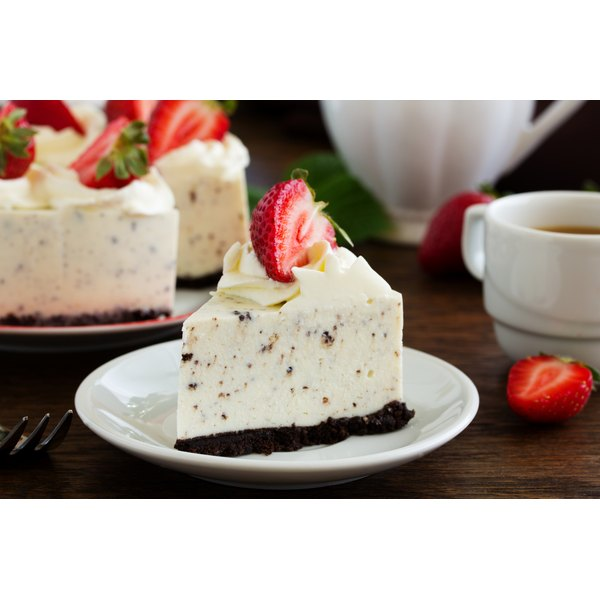 A slice of Oreo cheesecake with a strawberry on top.