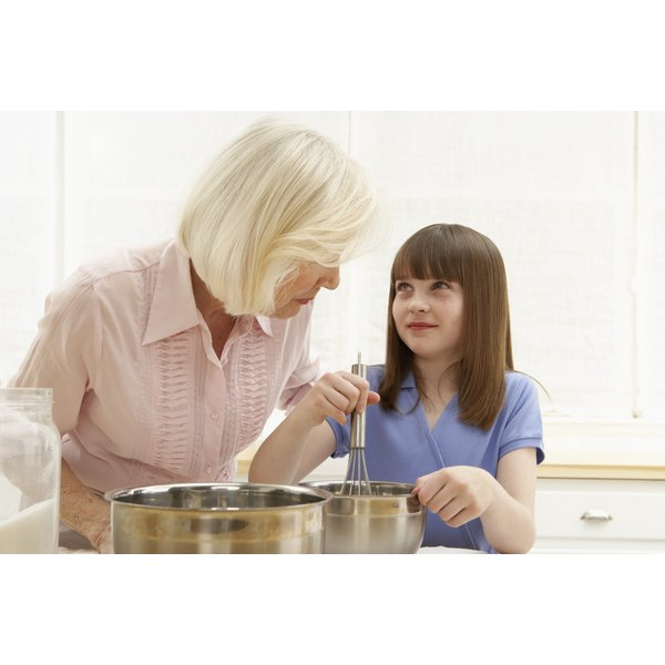 A grandmother and granddaughter baking together in the kitchen.