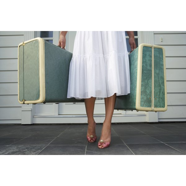 A close-up of a woman carrying two suitcases away from her front door across the porch.