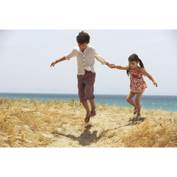 Two young children are playing on sand dunes.