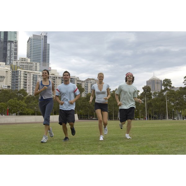 A group of four people jogging in a park.