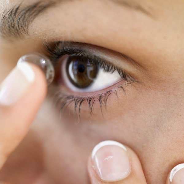 9294169b6a3 A woman putting in a contact lens. Contact lenses can cause a variety of eye  disorders ...