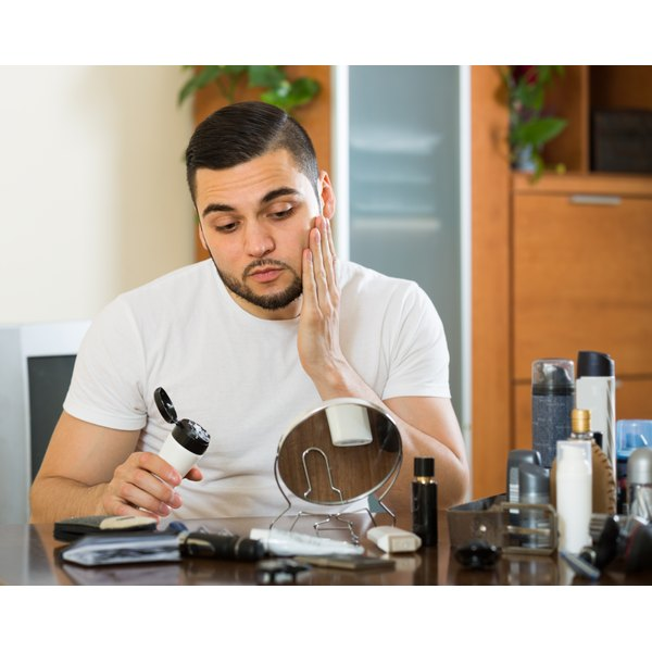 A man applies a moisturizing creme to his face in front of a mirror.
