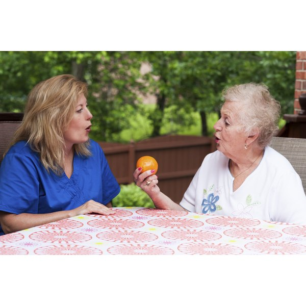 A speech therapist working with a patient on a patio.