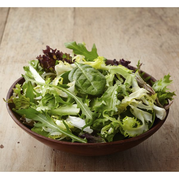 A wooden bowl with a salad of leafy greens.