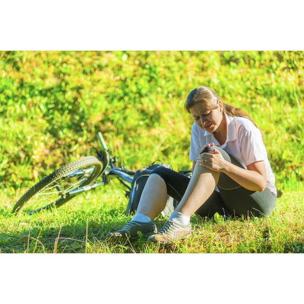 Woman sits in the grass with sore knees she got after a long bike ride.