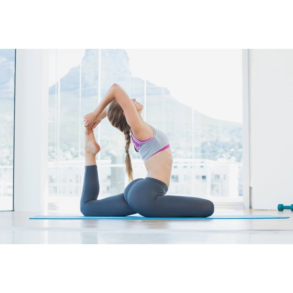 A woman is stretching in a yoga pose.